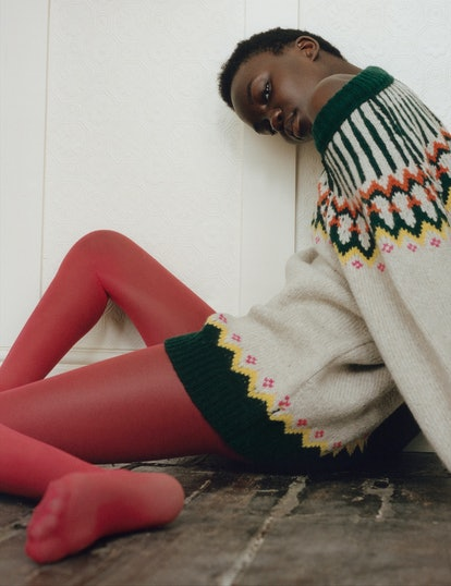 a woman in a fair isle sweater and red tights sitting on the floor