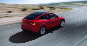Tesla Model Y driving down the road.