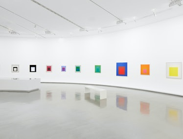 a row of colorful geometric paintings by josef albers in a white museum exhibition hall