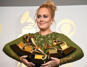 Adele holding an armful of Grammy awards