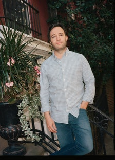 Danny Strong leaning against a staircase outdoors