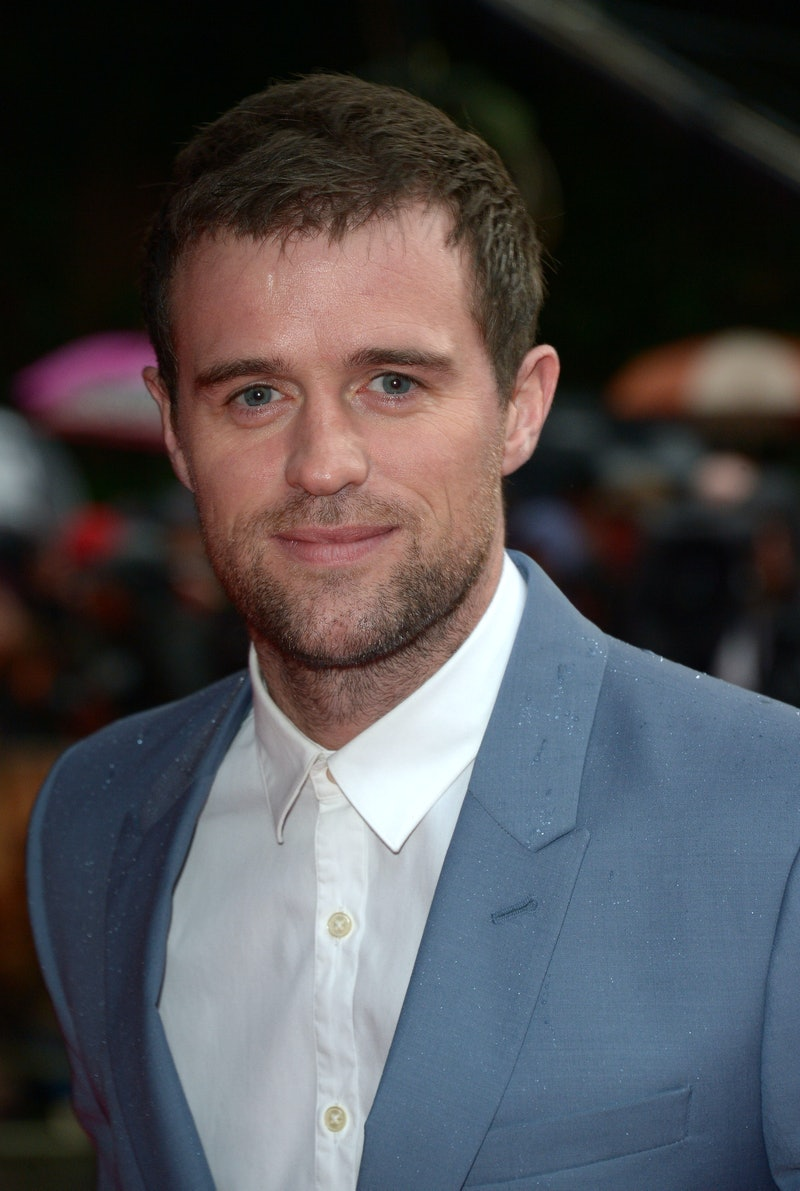Jonas Armstrong from The Drowning at a red carpet event wearing a blue/grey suit and white shirt