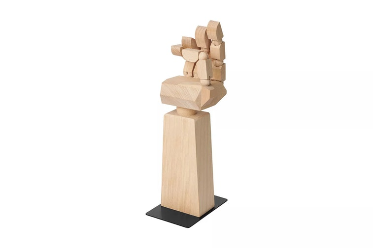 A wooden hand with half a forearm, the fingers pointing upward, can be seen on a white surface.