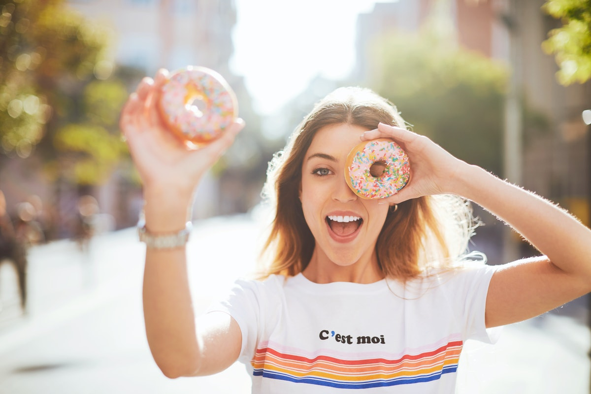Woman holding two sprinkled donuts