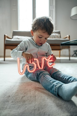 """young boy sitting on floor, holding a neon """"love"""" sign"""