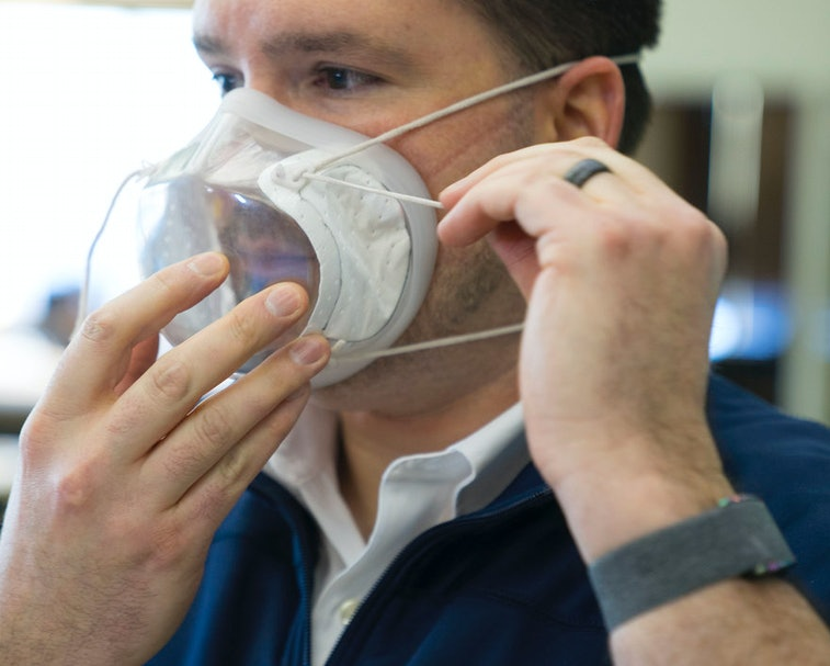 A man can be seen putting on a clear mask manufactured by Ford.