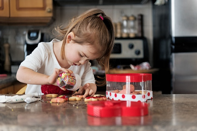 young girl making valentine's day cookies at kitchen counter