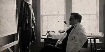 A black and white photo of Edward Page smoking a pipe in a lab coat