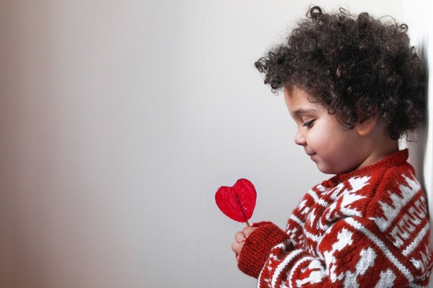 child holding and looking at a heart-shaped lollipop