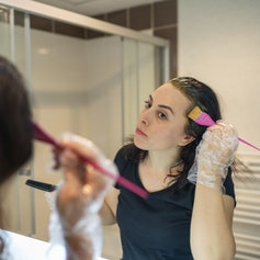 woman looking in the mirror, coloring her own hair