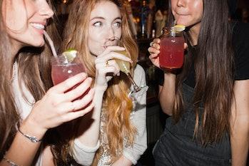 three young girls drinking at a bar