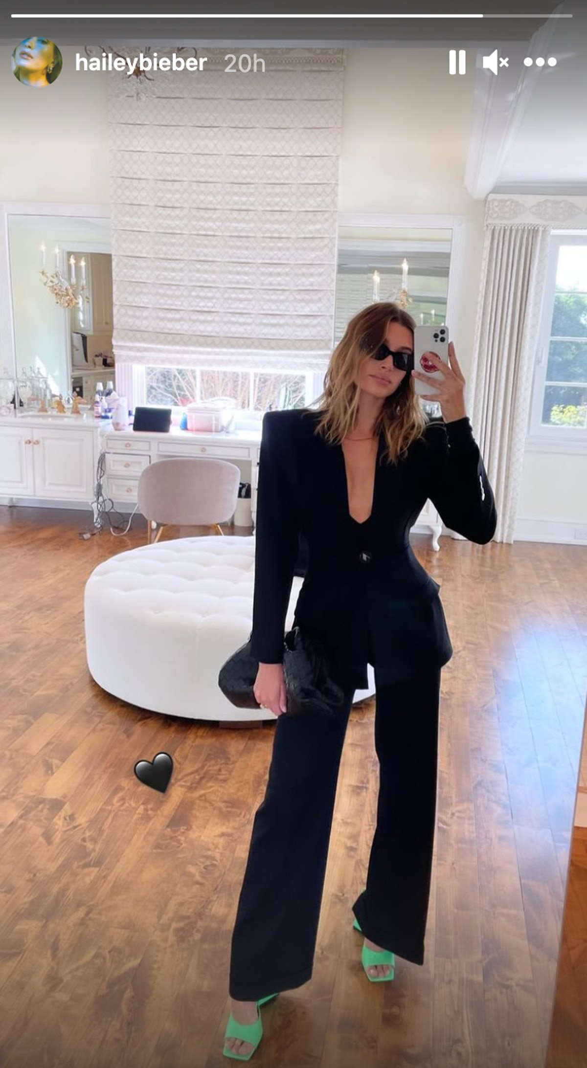 Hailey Bieber posts to Instagram Stories while wearing an Attico black blazer and pants combination.
