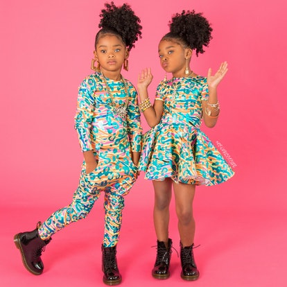 two girls in front of pink backdrop, one wearing jumpsuit the other in a dress both of which are in a colorful metalic leopard print