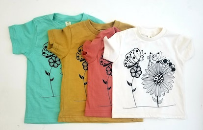 Four tee-shirts, each in a different size and color (white, red, mustard, and teal) with a black and white graphic of a bee and caterpillar on flowers