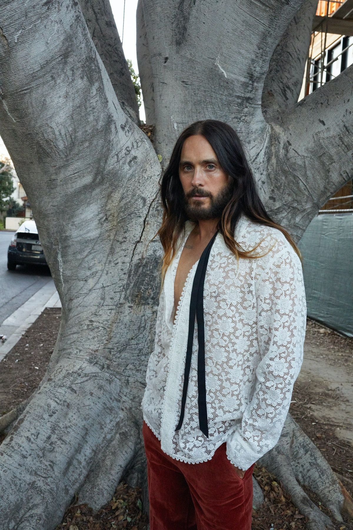 Jared Leto wears a Gucci shirt and pants.