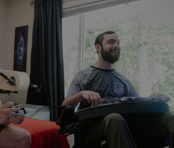 Two gamers are seen sitting together while playing on an Xbox console. One of the gamers is in a wheelchair.