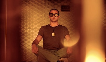 Cliff Curtis sitting cross-legged with goggles on.