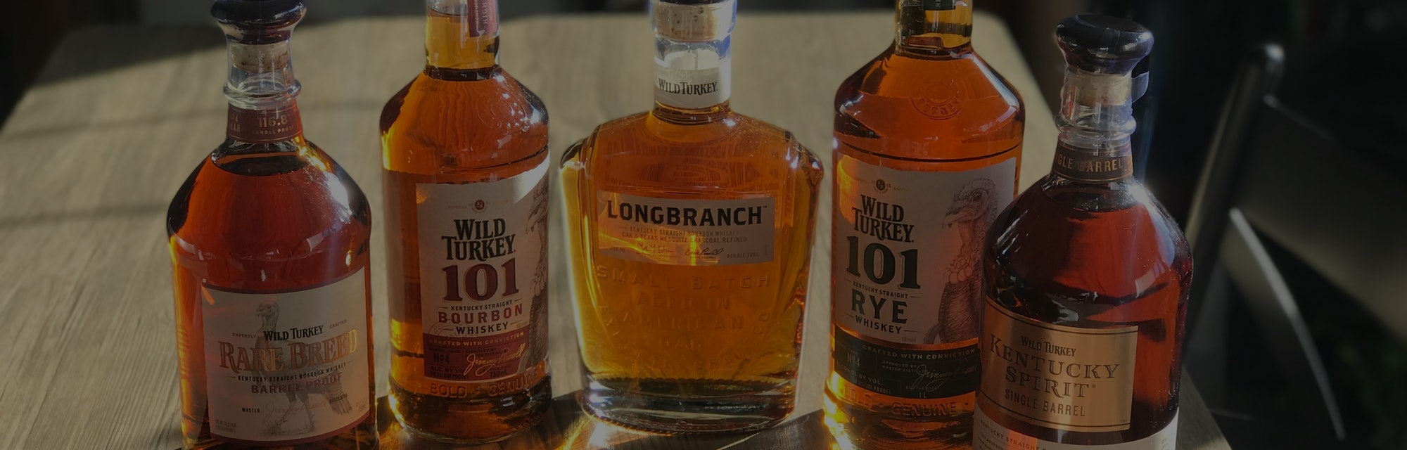 Five bottles of whiskey from the Wild Turkey Tasting company are shown on a dining table. There's a ...