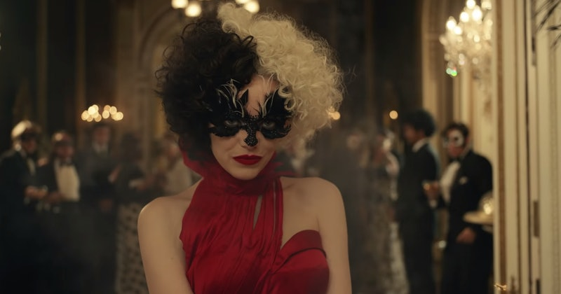 Emma Stone as Cruella in Disney's Cruella, wearing a red halter dress with a black eye mask and black and white wig
