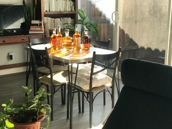 A dining table near a patio can be seen. There are five bottles of whiskey on top of the table. The sun is shining on the bottles, which causes them to cast deep orange and yellow lights on the surface of the table.