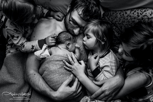 In a black and white photograph, a father cradles a swaddled newborn baby against his bare chest while three other children of various ages lay beside him and touch the baby. .
