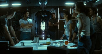 Seven cast members stand around a brightly lit table and argue in Sunshine