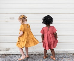 two kids wearing tiered linen dresses in mustard and pink