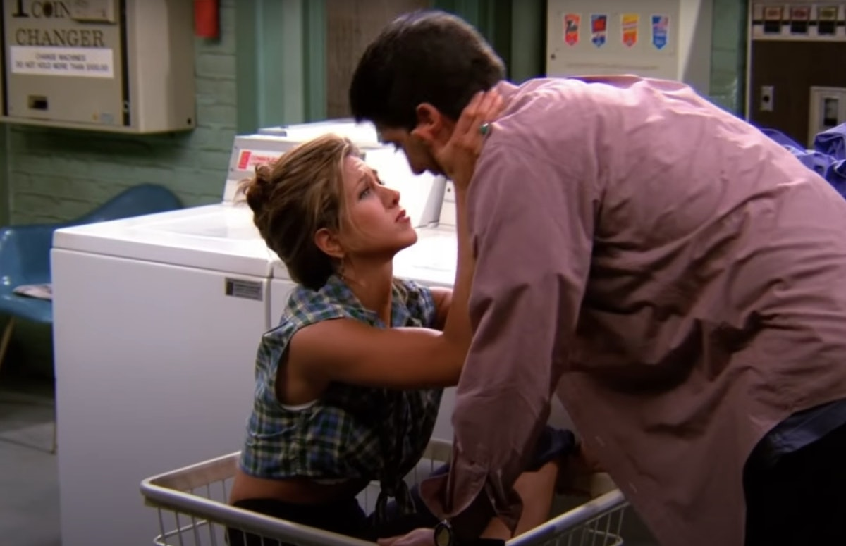 Rachel from 'Friends' sits in a laundry cart while wearing a hair clip and plaid crop top as she gets ready to kiss Ross.