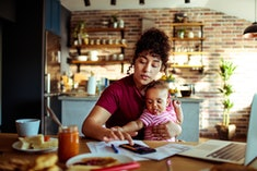 woman punching numbers into calculator while sitting at dining table with infant in her lap