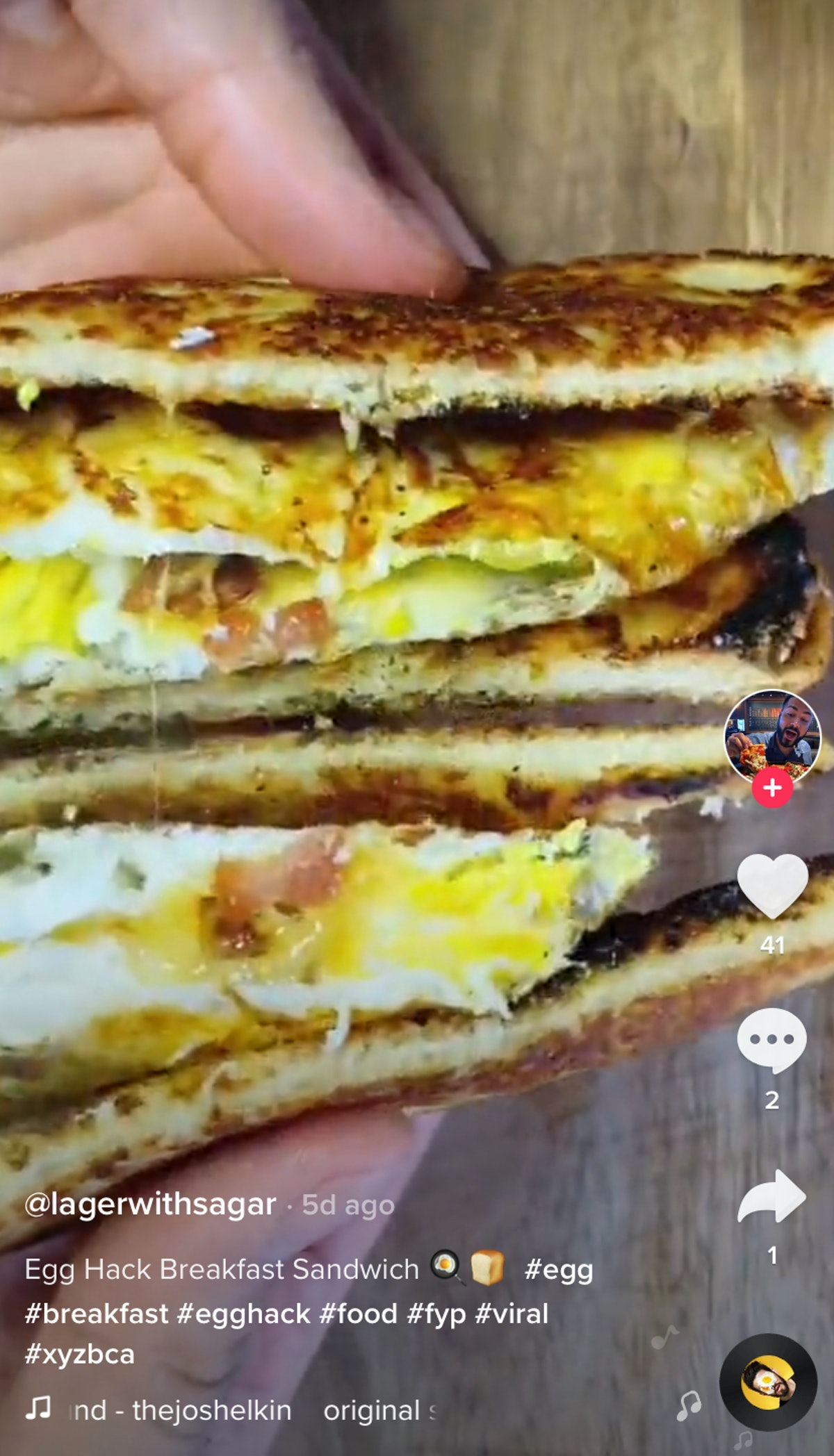 A man holds a egg hack breakfast sandwich from TikTok to show off the inside.