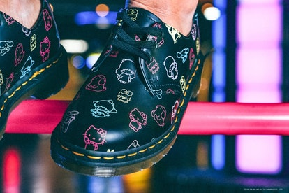 Dr. Martens x Hello Kitty 1461 boots being modeled in an arcade.