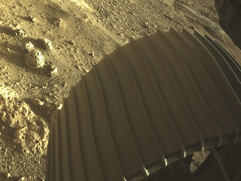 An image of the wheel of the Perseverance rover with interesting rocks nearby