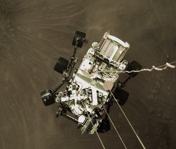 An image of the Perseverance rover as it descends to the surface of Mars.