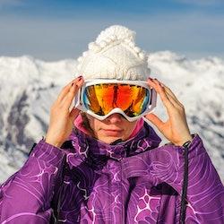 Skier adjusting goggles on slope
