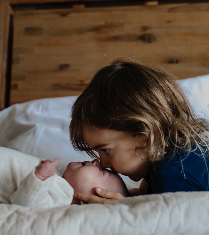 young child kissing newborn sibling on the forehead