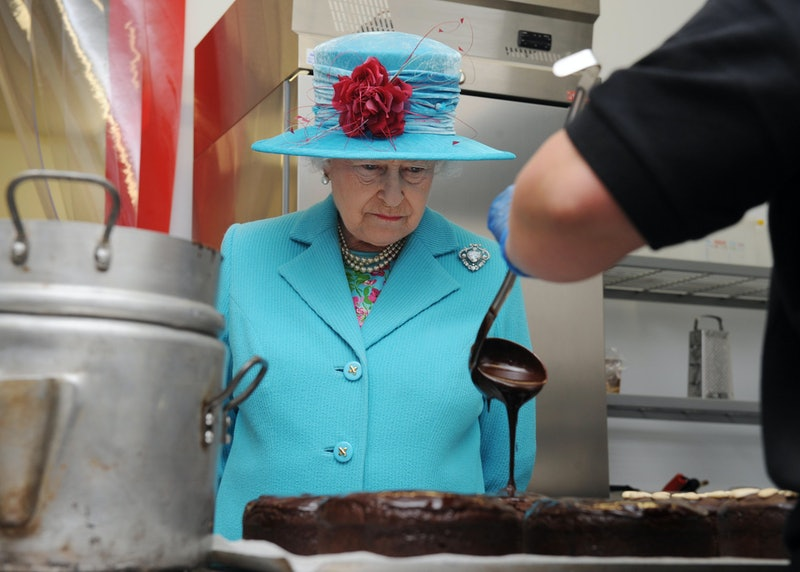 The queen watching a chocolate cake be made.