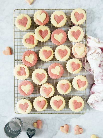 Cooling tray of pink and white sugar cookies with heart cutouts