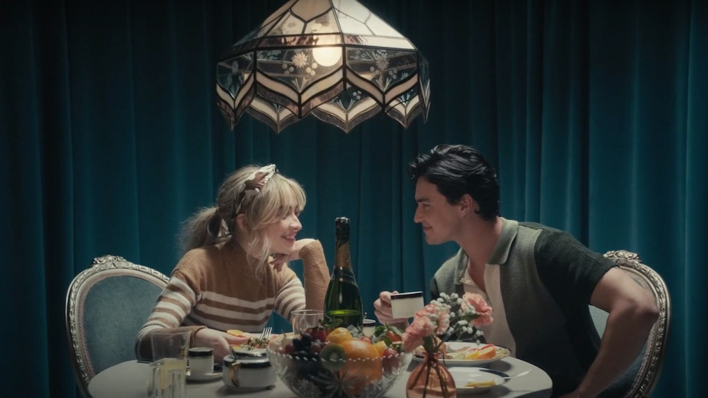 "Sabrina Carpenter sits at a lavish dinner table with co-star Gavin Leatherwood in the ""Skin"" music video."