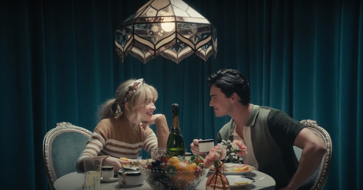 """Sabrina Carpenter sits at a lavish dinner table with co-star Gavin Leatherwood in the """"Skin"""" music video."""