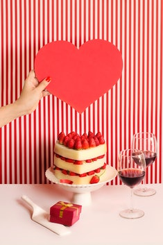 Heart-shaped cake, layered, with strawberries; sitting on white cake stand in front of red and white striped wall; arm holding a big red heart over the cake; two glasses of red wine beside the cake and a cake server with a red present on the other side