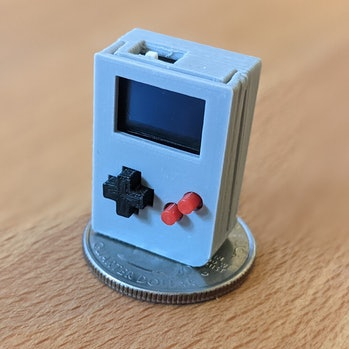 A tiny Game Boy clone is placed on an American quarter. If made to stand on the coin, the clone won't cover the coin.