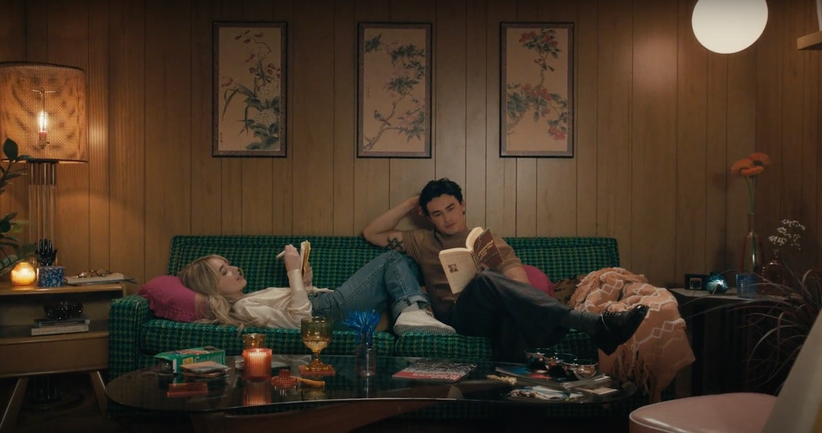 """Sabrina Carpenter journals on the couch while Gavin Leatherwood reads a book during the """"Skin"""" music video."""