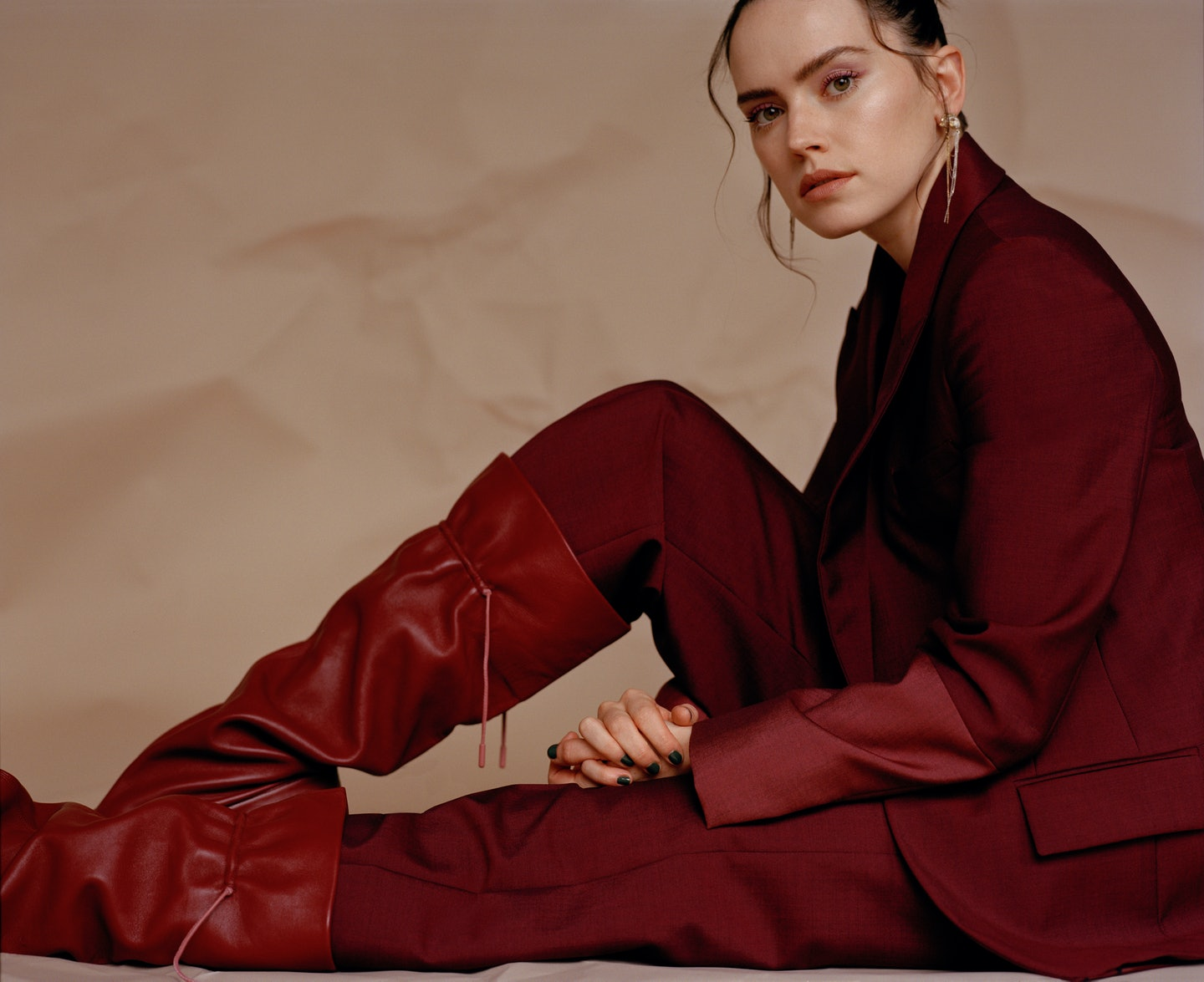 TZR cover star Daisy Ridley appears sitting down while wearing an all red Roksanda suit.