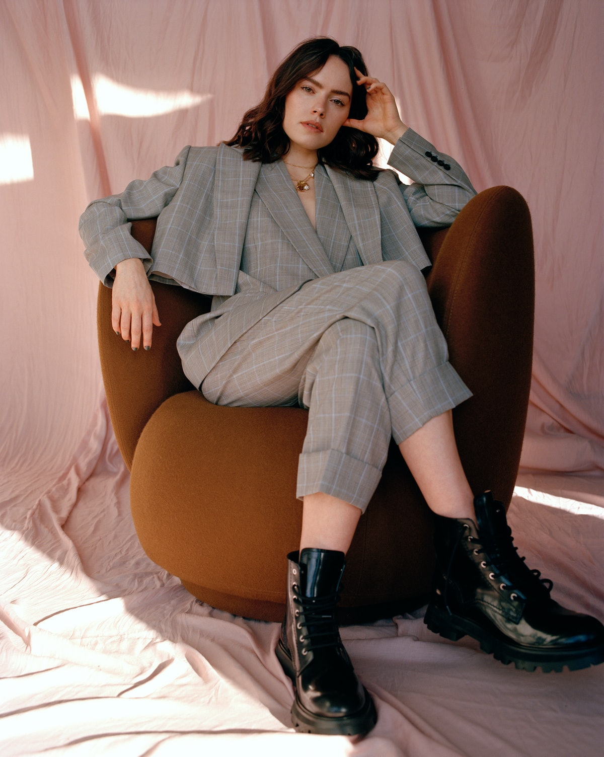 TZR cover star Daisy Ridley sitting down in a chair wearing a gray suit by Alexander McQueen.