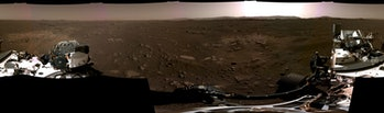 A panoramic view of Mars which includes some parts of the rover with the sun over the horizon