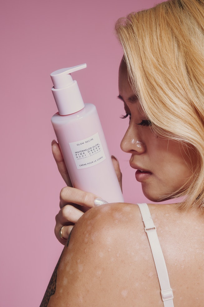 Person posing with a bottle of Glow Recipe Watermelon Glow Pink Dream Body Cream