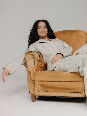 'It's A Sin' star Lydia West poses in a chair for Bustle UK.