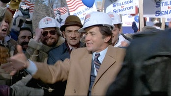 Martin Sheen as Greg Stillson, wearing a hardhat amidst a crowd on the campaign trail.