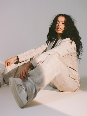 'It's A Sin' star Lydia West sits on the ground in a studio wearing an all white outfit.