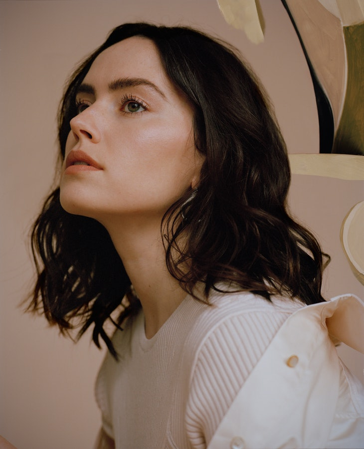 A closeup shot of Daisy Ridley in profile, who wears all white in a TZR cover shoot.